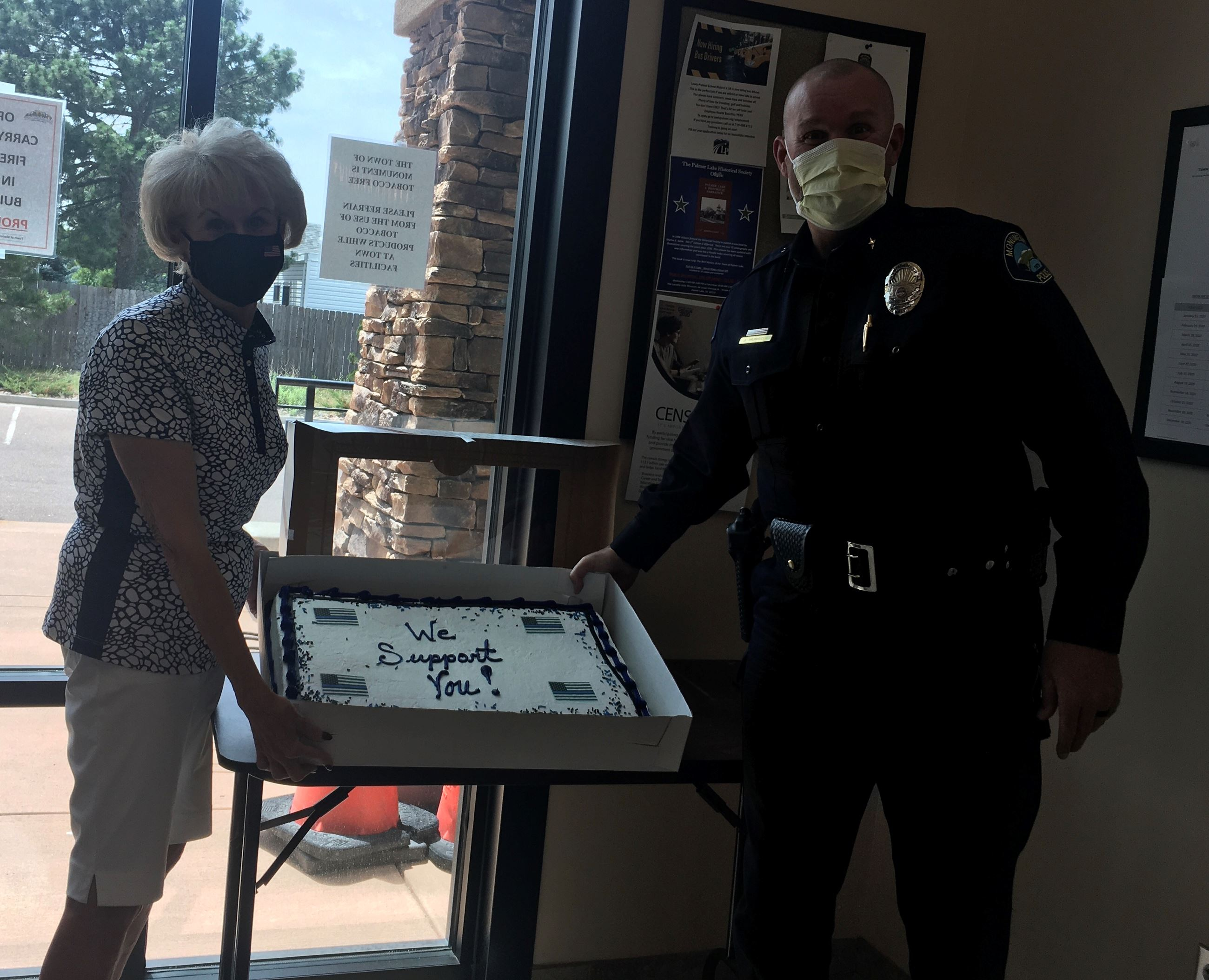 woman and police officer standing with cake by a window